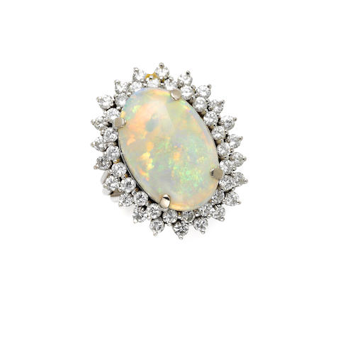 An oval opal, round brilliant cut diamond and 14 karat white gold ring