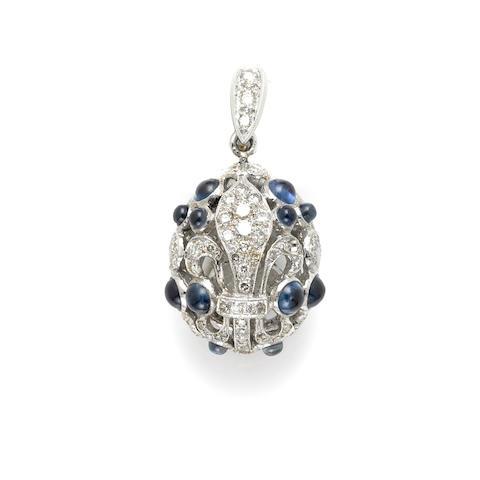 A cabochon sapphire, round brilliant cut diamond and 18 karat white gold 'fleur di lis' pendant