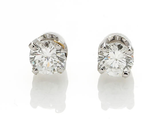 A pair of diamond and 14k white gold solitaire earrings