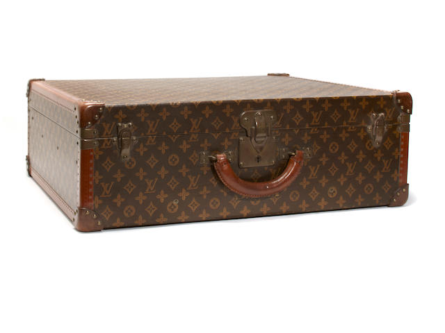A Louis Vuitton hard sided suitcase