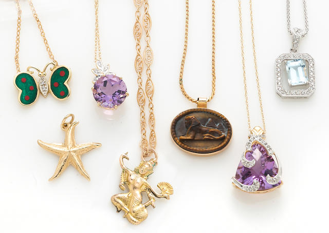 A collection of seven amethyst, tiger's eye, aquamarine, diamond, enamel, and 14k white and yellow gold pendants, six with chains