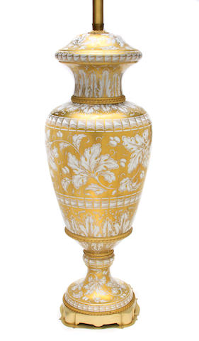 A French gilt heightened porcelain urn mounted as a table lamp