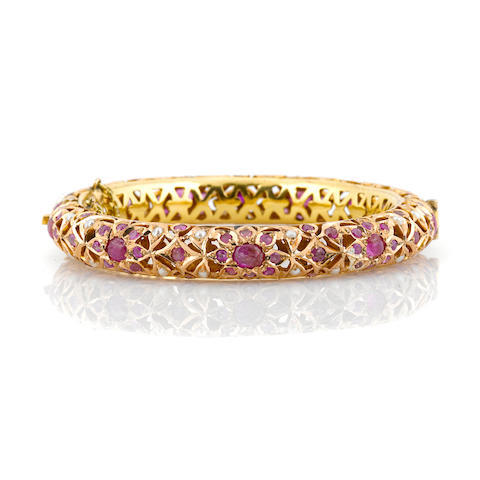 A ruby, lead glass filled ruby, seed pearl and 14k gold bangle bracelet