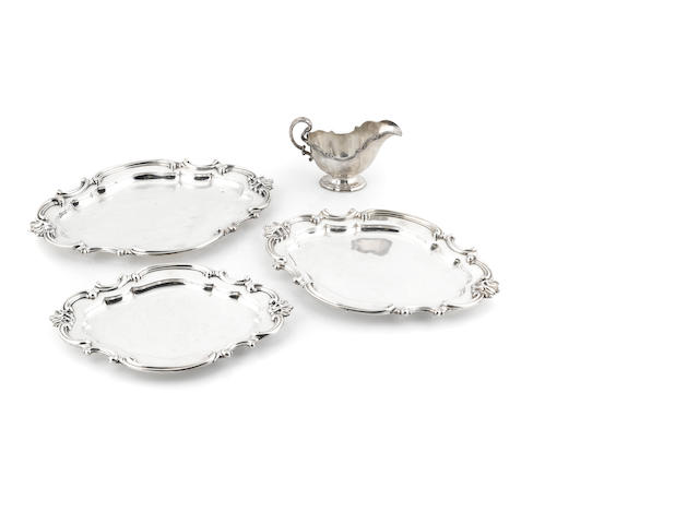 a group of three graduated silverplate trays and a sauceboat