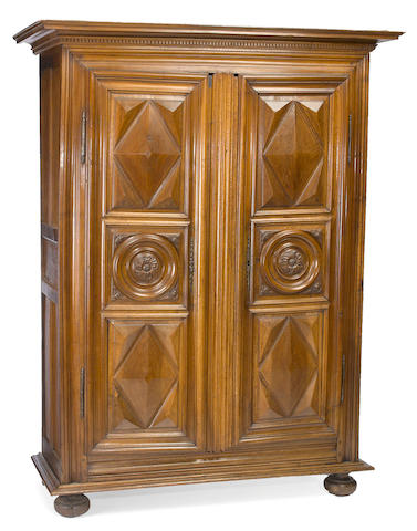 A Louis XIV walnut panel front armoire on suppressed front ball feet <BR /> early 18th century