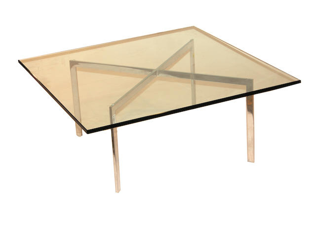 A contemporary chromed metal and glass top coffee table