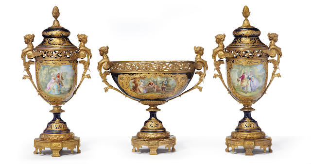 A Louis XVI style 'Sèvres' bleu du roi ground gilt bronze mounted gilt and polychrome decorated three piece garniture <BR />fourth quarter 19th century
