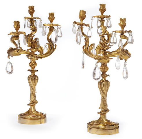 A pair of Louis XV style gilt bronze and rock crystal three light candelabra <BR />fourth quarter 19th century
