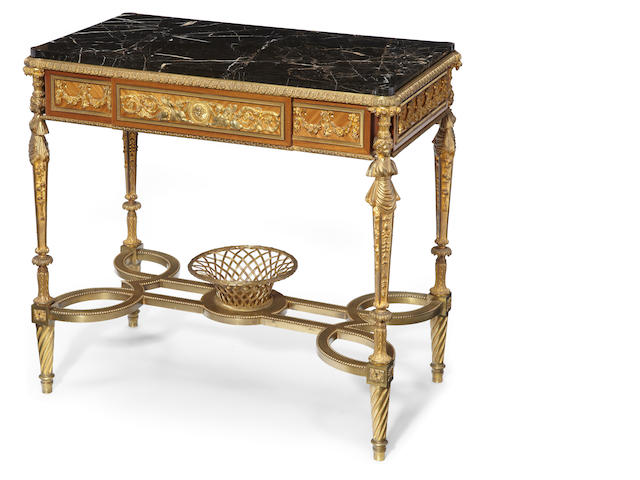 A Louis XVI style gilt bronze mahogany and kingwood center table <BR/>after Adam Weisweiller<BR/>late 19th century
