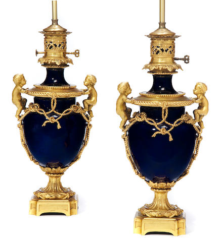 A pair of Louis XVI style gilt bronze mounted bleu du roi porcelain two-handled urn-form oil lamps <BR />fourth quarter 19th century