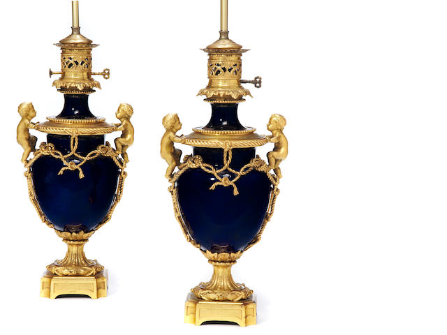 A pair of Louis XVI style gilt bronze mounted bleu du roi porcelain oil lamps <BR />fourth quarter 19th century