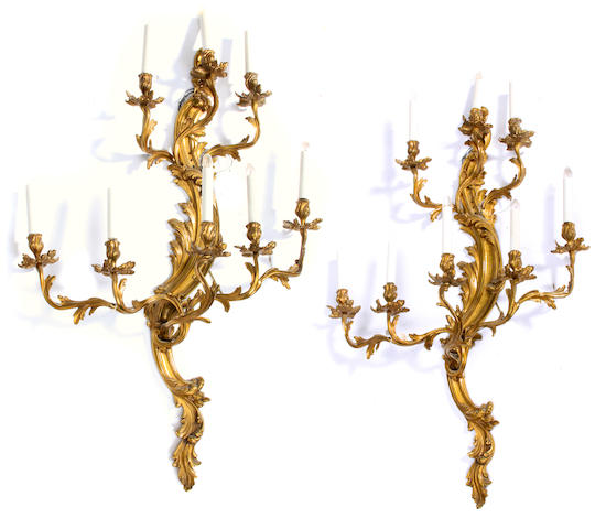 A pair of Louis XV style gilt metal three light bras de lumière