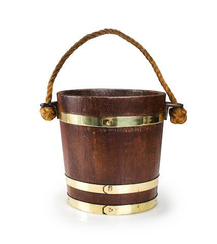 A brass bound water bucket<BR /> 12 x 12 in. (30.4 x 30.4 cm.) height x diameter.