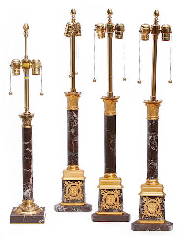 A group of four gilt metal and marble columnar form table lamps