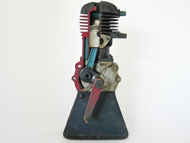 A singe cylinder, two stroke cutaway engine.
