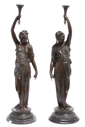 A pair of patinated bronze figures of maidens