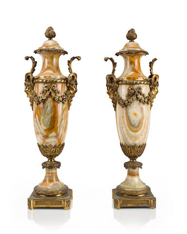 A pair of Neoclassical style gilt-bronze-mounted onyx covered urns