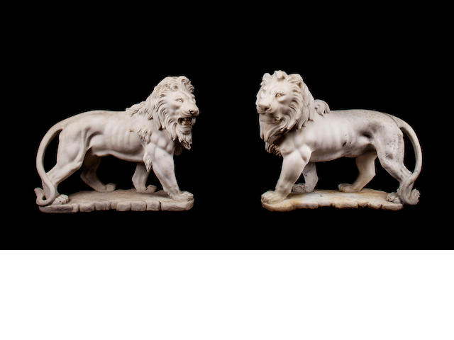 A pair of South Italian carved white marble figures of recumbent lions
