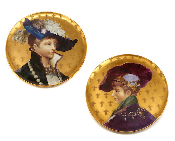 A pair of French polychrome gilt ground porcelain portrait chargers