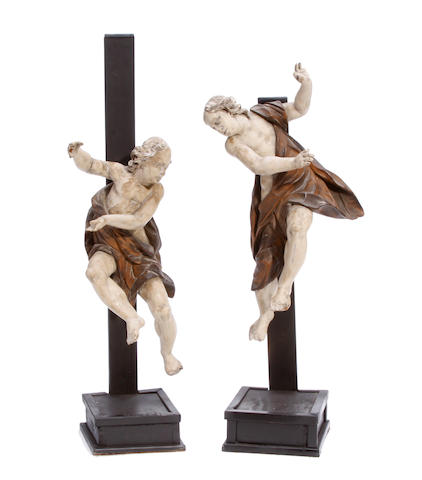 A pair of German Baroque paint decorated figures of angels on later stands