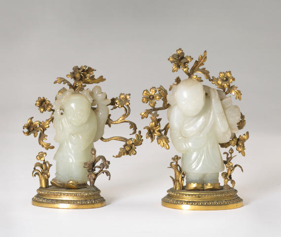 A pair of very small white nephrite jade boys in gilt metal floral mounts
