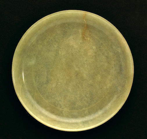 A pale translucent yellow-green nephrite saucer with upturned rim and recessed base 18th century