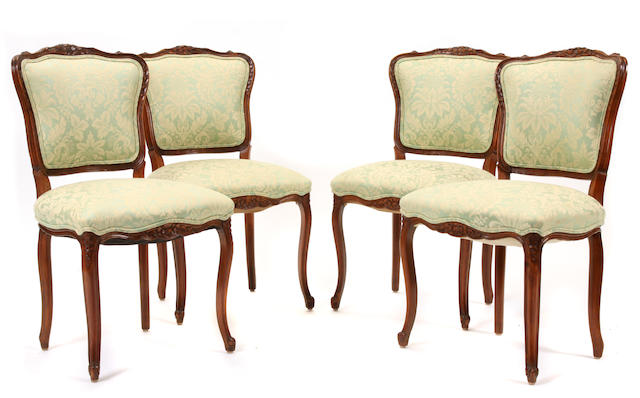 A set of four Louis XV style carved walnut side chairs