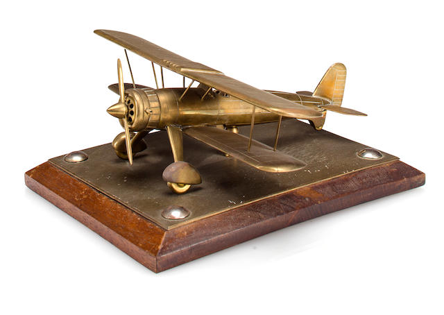 A Stearman (Boeing) brass model bi-plane   1940s 10 x 10 in. (25.4 x 25.4 cm.) length x wingspan.