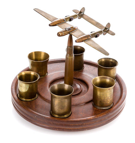 A brass P-38 fighter, with 6 shot glasses  dated 1945 diameter 10 in. height 8 in.