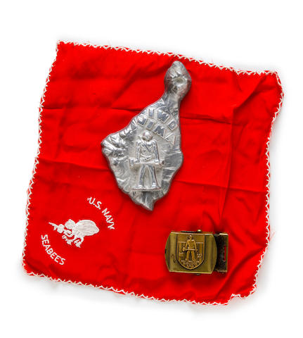 Iwo Jima Seabees Group: one red handkerchief; a Seabees brass belt buckle; a solid aluminum model of the Island of Iwo Jima featuring a Seabee; an embroidered cushion cover or banner with the Seabees logo (designed by Walt Disney during WWI)