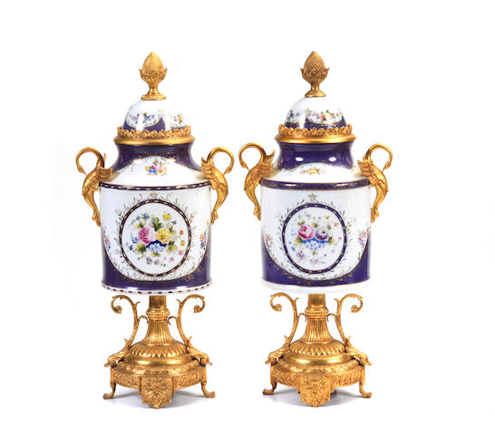 A pair of Neoclassical style gilt metal mounted covered porcelain urns