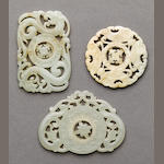 A group of three reticulated jade plaques with movable center medallions