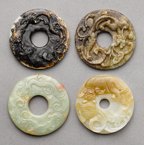 A group of four jade bi with raised relief decoration