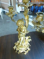 A pair of Louis XV style gilt bronze figural three-light candelabra <BR />fourth quarter 19th century