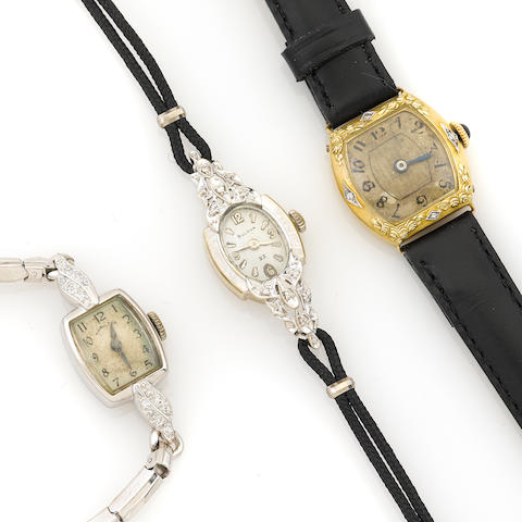 A collection of three diamond and 14k cased watches