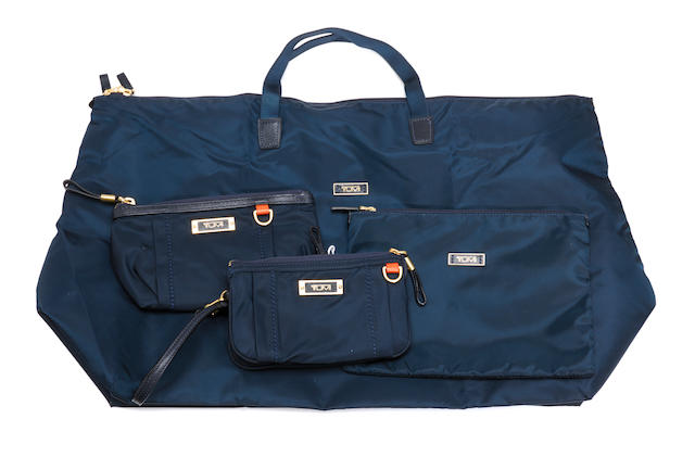 A Tumi navy blue set of travel bags