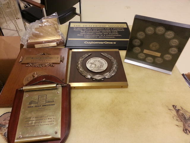 An assortment of Chrysler and Good Year Tire plaques and awards.