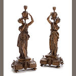 A pair of Continental patinated metal figural candlesticks