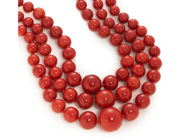 A coral graduated three-strand necklace