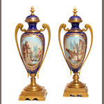 A pair of Continental gilt bronze and porcelain covered urns