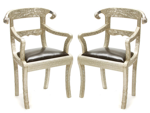 A pair of Indian stamped metal and custom black leather upholstered armchairs