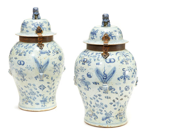 A pair of patinated metal mounted Chinese blue and white covered urns in the English taste