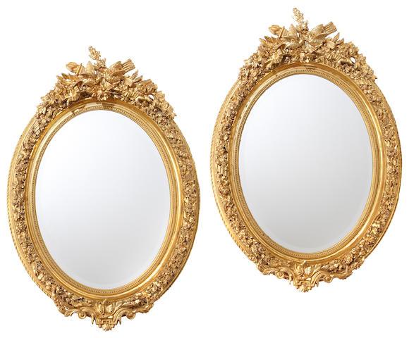A pair of Napoleon III style giltwood and gilt composition oval mirrors late 20th century