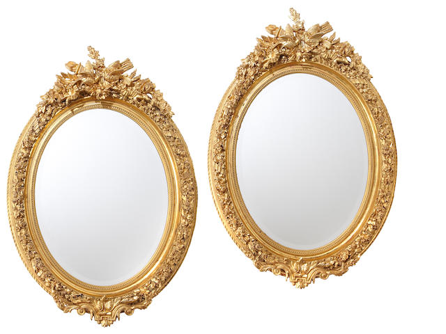 A pair of Napoleon III style giltwood and gilt composition oval mirrors