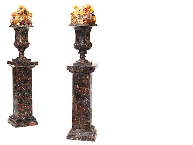 A pair of Neoclassical style brown, black and tan urns on pedestals with multi-color marble fruit and flowers
