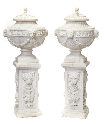 A pair of Neoclassical style white marble covered urns on pedestals