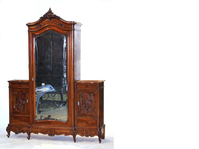 A Louis XV style walnut bedroom suite comprised of an armoire, a bed, a pair of stands, and a mirror