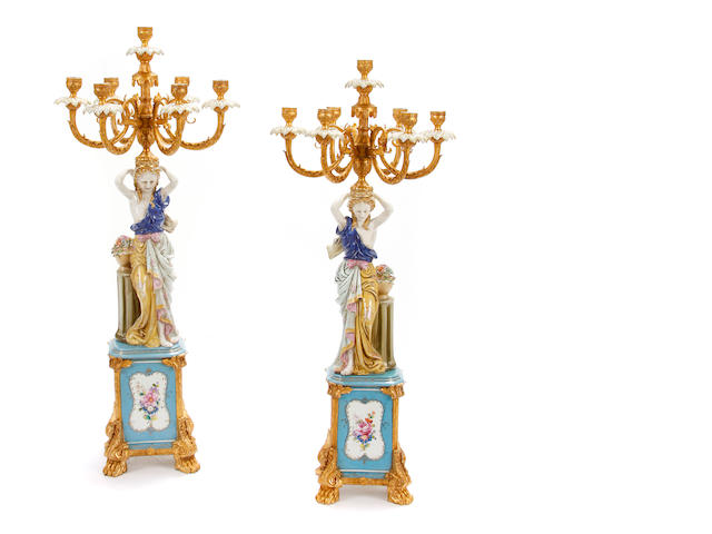 A pair of Rococo style gilt metal mounted porcelain figural candelabra