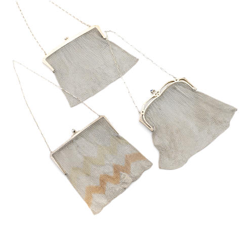 A collection of three silver mesh purses