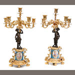A pair of French gilt and patinated bronze and porcelain mounted six light candelabra